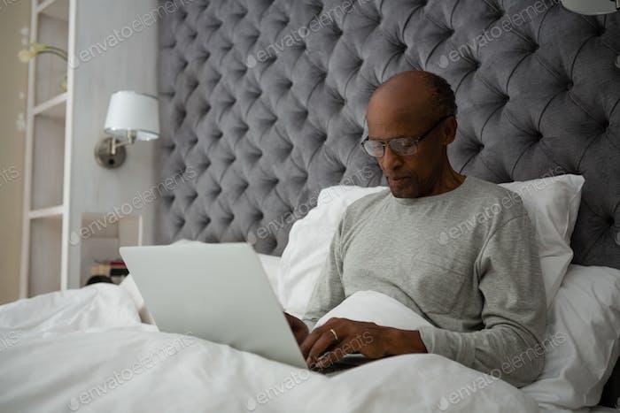 Senior man using laptop while sitting on bed
