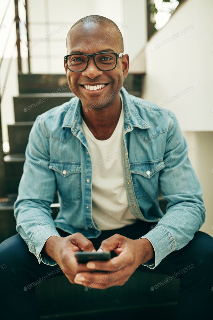 Smiling African businessman sitting on office stairs sending text messages