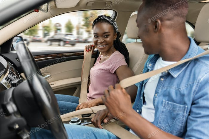 Smiling african amerfican man and woman fastening seat belts