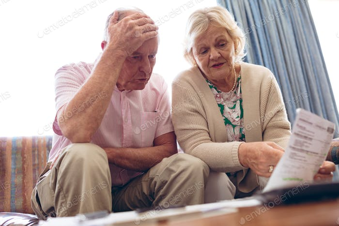 Worried senior couple discussing over medical bill while sitting on sofa at retirement home