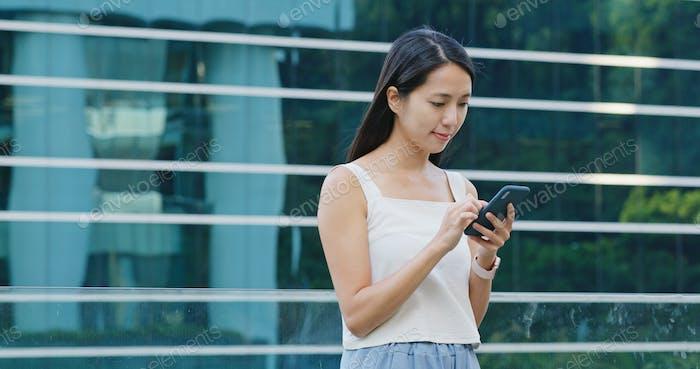 Frau Nutzung des Mobiltelefons mit dem Bürogebäude Hintergrund