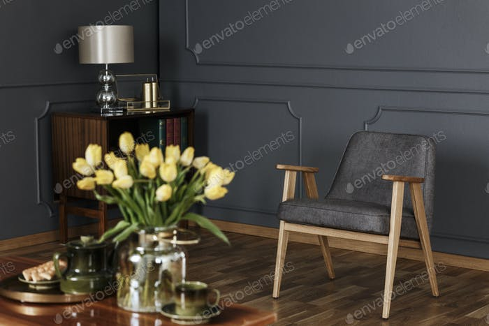 Real photo of a retro gray armchair and wooden cabinet against a